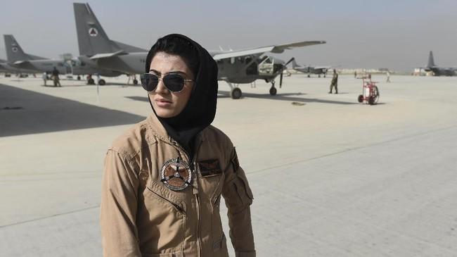 Mengenakan seragam khas pilot, kaca mata penerbang dan jilbab hitam, perempuan berusia 23 tahun ini menjadi pusat perhatian di Pangkalan Angkatan Udara Kabul. (AFP Photo/ShahMarai)