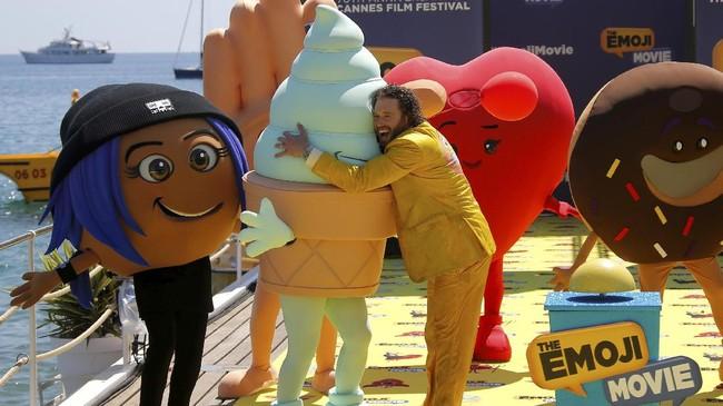 <p>Film <em>The Emoji Movie</em> yang dijadwalkan tayang tahun ini, memberi gimmick dengan figur emoji. Aktor TJ Miller berpose di sana, memeluk satu di antaranya. (REUTERS/Stephane Mahe)</p>