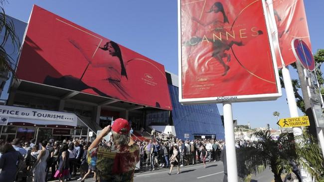 <p>Sementara di sekitar lokasi, para wisatawan berfoto dengan latar poster besar Cannes. Selain didatangi selebriti, festival itu memang mengundang perhatian wisatawan. (REUTERS/Eric Gaillard)</p>