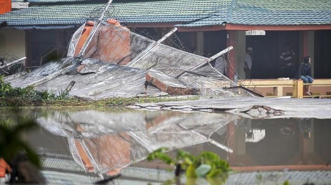 <p>Sejumlah warga binaan berada di samping dinding yang jebol akibat banjir di Lapas Klas II A Jambi, Jambi, Rabu (14/6). Dinding lapas jebol akibat banjir setelah hujan deras mengguyur daerah itu. (ANTARA FOTO/Wahdi Septiawan)</p>