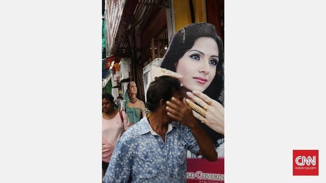 <p>Poster iklan menjadi salah satu bagian elemen fotografi jalanan. Menunggu orang lewat dengan gestur tangan yang sama dengan gestur tangan poster perempuan membentuk kesan kesamaan dalam fotografi jalanan.</p>