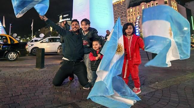 <p>Pendukung timnas Argentina di Buenos Aires merayakan sukses Lionel Messi dan kawan-kawan lolos ke Piala Dunia 2018. Argentina lolos bersama Brasil, Uruguay, dan Kolombia. (AFP PHOTO / EITAN ABRAMOVICH)</p>