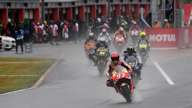 Pebalap Repsol Honda Marc Marquez memimpin grup pebalap MotoGP keluar dari pit pada latihan bebas MotoGP Jepang. Marquez menjadi yang tercepat dengan mengalahkan Aleix Espargaro. (AFP PHOTO/Toshifumi KITAMURA)