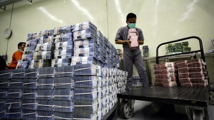 BUMN percetakan uang, Perum Peruri dibanjiri pesanan cetak uang dari Bank Indonesia (BI). Pihak Peruri mengaku sangat kewalahan untuk memenuhi pesanan uang dari BI yang mencapai miliaran lembar. Seorang petugas tampak merapihkan tumpukan uang di cash center Bank Negara Indonesia Pusat, kawasan Sudirman, Jakarta, Senin (21/10/2013). (FOTO: Rachman Haryanto/detikFoto)