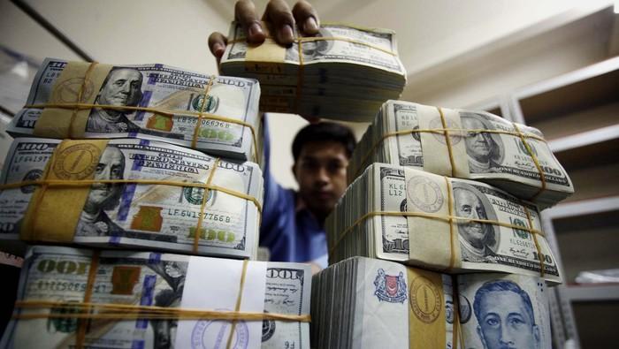 Pekerja merapihkan uang Dollar dan Rupiah di Cash Center BRI Pusat, Jakarta, Kamis (5/6/2014). Nilai tukar rupiah hingga penutupan perdagangan sore pekan ini hampir menyentuh angka Rp 12.000 per-dollar US.