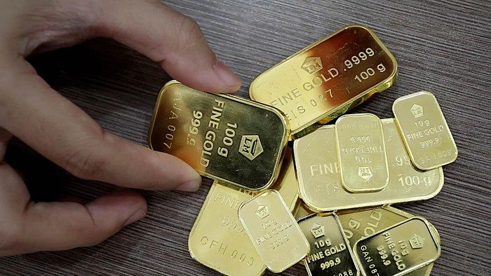 Seorang customer service Bank BNI Syariah cabang Benhil Jakarta Pusat menunjukkan logam mulia emas batangan berukuran 10 dan 100 gram, akhir pekan lalu. Berdasarkan data Asosiasi Pengusaha Emas dan Permata Indonesia, penjualan emas terus meningkat meskipun nilai tukar rupiah anjlok terhadap dollar AS. Jakarta (8/26/2013)