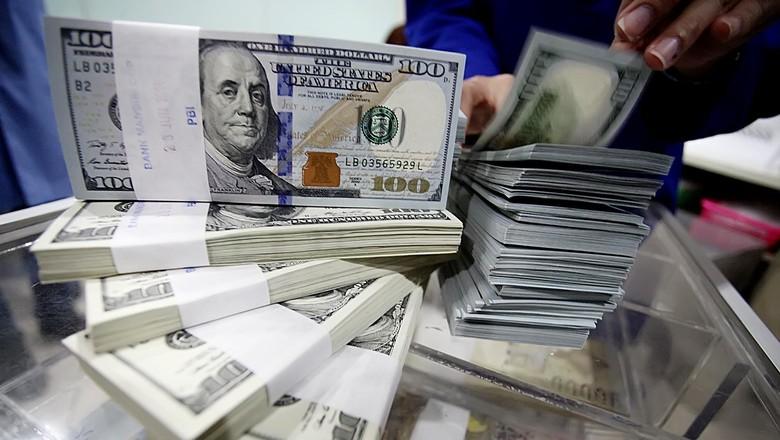 Seorang petugas menata uang dollar di Jakarta, Senin (30/6/2014). Nilai tukar dolar Amerika Serikat (AS) terus menguat terhadap rupiah sehingga mendorong minat masyarakat untuk berburu mata uang negeri Paman Sam ini.