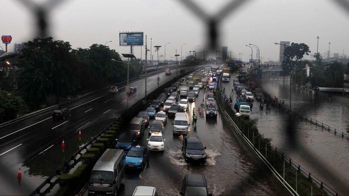 Warga berusaha melintasi genangan banjir yang melanda ruas jalan tol Pluit-Tomang, Jakarta, Kamis (17/1). Akibat banjir yang merendam ruas tol menyebabkan kemacetan dan ruas jalan sulit dilalui. File/detikFoto.
