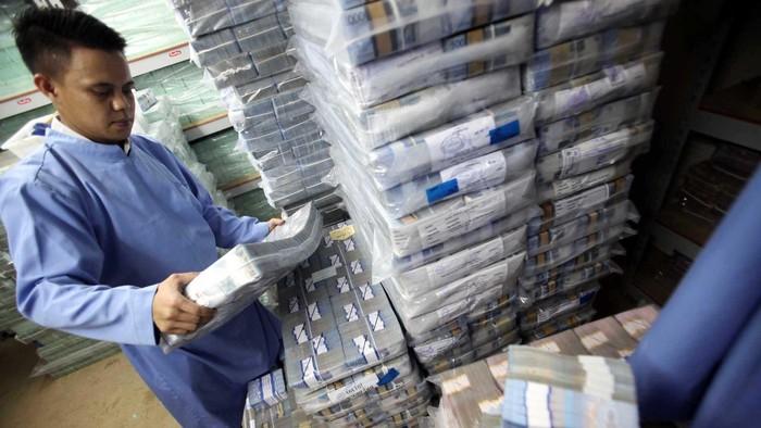 Seorang petugas mengangkut uang rupiah di sentra kas Bank BRI, di Jakarta, Rabu (28/8/2013). Melemahnya nilai tukar rupiah terhadap dollar Amerika Serikat membuat beban utang luar negeri bertambah. File/detikFoto.