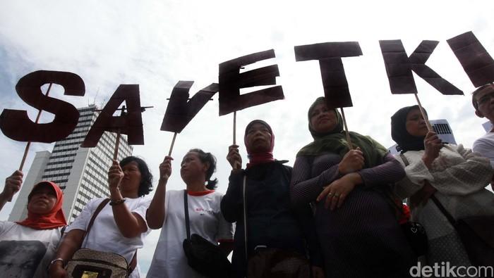 Puluhan aktivis yang tergabung dalam Migran Care melakukan aksi teatrikal Save TKI di Bundaran HI, Jakarta, Selasa (18/12).