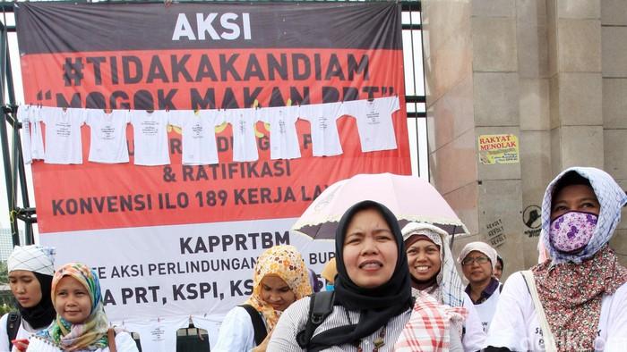 Sekitar 50 orang yang tergabung dalam Komite Aksi Perlindungan Pekerja Rumah Tangga dan Buruh Migran berunjuk rasa di depan Gedung DPR/MPR, Jalan Gatot Subroto, Jakarta Pusat, Selasa (13/1/2015). Mereka berunjukrasa sambil membawa replika dan sikat raksasa.