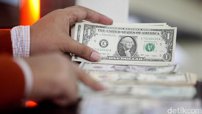 Nilai tukar rupiah terhadap dolar Amerika Serikat (AS) hari ini menguat cukup tajam. Dolar AS kini telah meninggalkan level Rp 12.900. Penguatan rupiah tidak lepas dari pelemahan dolar AS secara global. Dollar Index (perbandingan dolar AS terhadap 6 mata uang utama dunia) tercatat melemah 0,38% ke 98,355. Bahkan Dollar Index sempat menyentuh 98,216, terendah dalam sepekan terakhir. Seorang nasabah membeli mata uang dolar AS di Bank BNI Jakarta Pusat, Kamis (16/04/2015). Rengga Sancaya/detikcom.