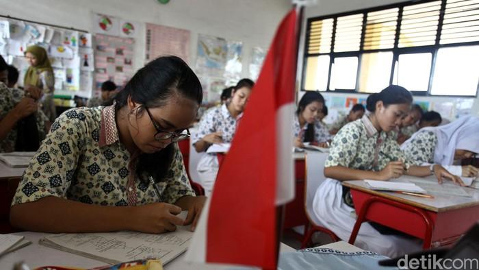 Akibat gedung sekolah terbakar, siswa-siswi SMPN 65 Jakarta Utara terpaksa mengungsi ketika belajar. Mereka untuk sementara harus belajar di gedung milik SDN 12 Pagi Jakarta Utara. Para siswa SMPN 65 Jakarta Utara mengangkat bangku dan kursi menuju ruang kelas di SDN 12 Pagi Jakarta Utara, Kamis (16/04/2015). Grandyos Zafna/detikcom