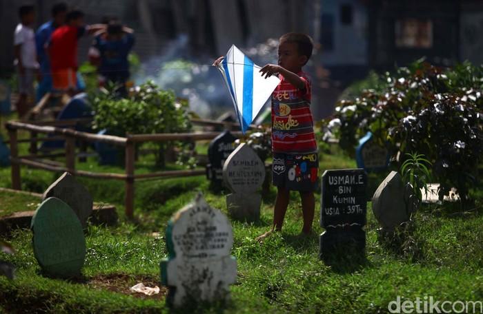 Sejumlah anak bermain layang-layang di atas sebuah makam di Tempat Pemakaman Umum (TPU) Prumpung, Jakarta Timur, Minggu (23/6). Minimnya lahan bermain dan ruang terbuka hijau di Jakarta membuat sejumlah anak menjadikan tempat pemakaman umum sebagai lahan bermain mereka. Agung Pambudhy/Detikcom. File/detikFoto.