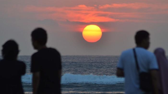 Sejumlah wisatawan menyaksikan matahari terbit (sunrise) di Pantai Sanur, Bali, Rabu (6/5). Panorama matahari terbit yang indah menjadi daya tarik wisatawan yang berkunjung ke Pantai Sanur pada pagi hari. ANTARA FOTO/Fikri Yusuf/Rei/ama/15.