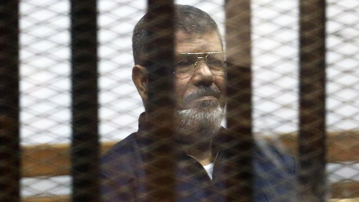 Deposed Egyptian President Mohamed Mursi listens to his verdict behind bars at a court on the outskirts of Cairo, Egypt June 16, 2015. An Egyptian court sentenced Mursi to death on Tuesday on charges of killing, kidnapping and other offences during a 2011 mass jail break.The general guide of the Muslim Brotherhood, Mohamed Badie, and four other Brotherhood leaders were also handed the death penalty. More than 80 others were sentenced to death in absentia. REUTERS/Asmaa Waguih