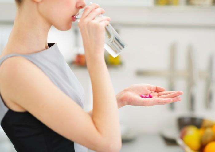 Ilustrasi seorang wanita yang sedang mengonsumsi vitamin atau suplemen