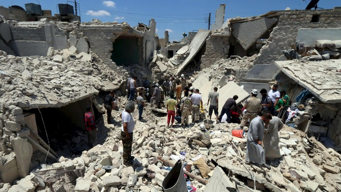 Civil defence members and civilians search for survivors under the rubble of a site hit by what activists said were barrel bombs dropped by forces loyal to Syrias President Bashar al-Assad in Aleppo, Syria June 21, 2015. REUTERS/Abdalrhman Ismail