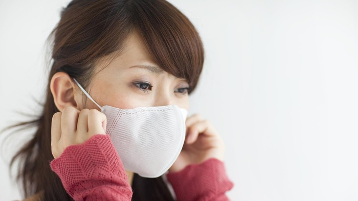Seorang perempuan mengenakan masker putih.