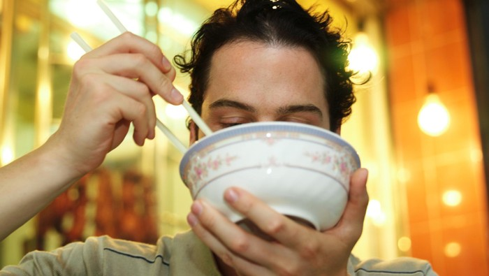 seorang pria sedang asyik makan menggunakan mangkuk