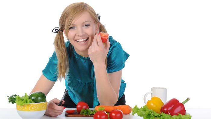 Seorang wanita tampak makan buah dan sayur. Foto: Thinkstock