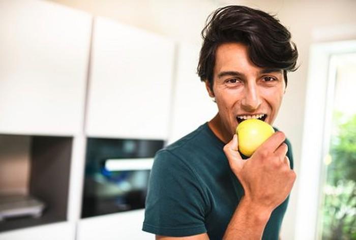 pria muda memakan sebutir apel hijau