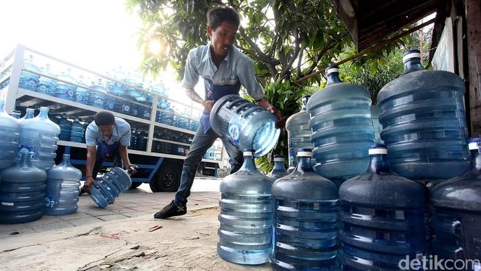 Permintaan air minum dalam kemasan mengalami lonjakan saat perayaan hari besar seperti pada saat Hari Raya Idul Fitri seperti saat ini. Lonjakan tersebut dinilai wajar karena memang kebutuhan masyarakat akan air minum dalam kemasan mengalami kenaikan dengan alasan praktis. Petugas tengah memindahkan galon-galon air dari truk di jalan RA Kartini, Kota Bekasi, Rabu (22/07/2015). Rengga Sancaya/detikcom.