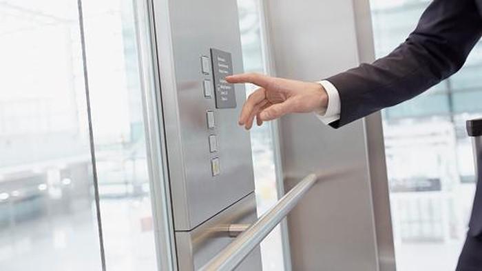 Hand of businessman pressing control in elevator