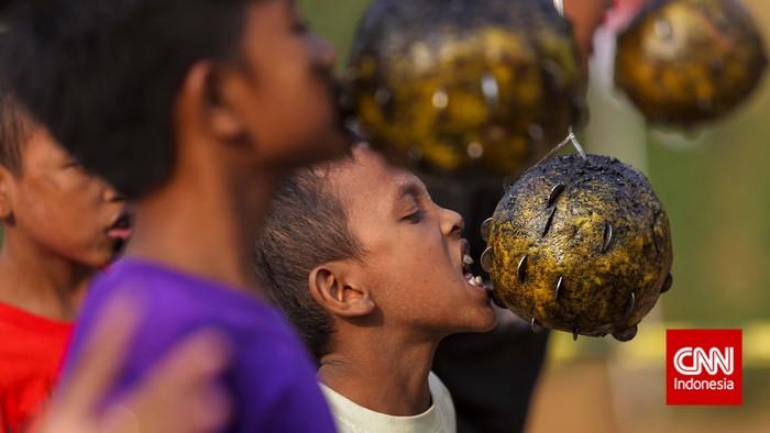 Anak-anak mengikuti perlombaan khas 17-an gigit koin yang digelar dalam acara festival Ciliwung di Jakarta, Selain memperingati Hari Kemerdekaan, Festival Ciliwung diadakan untuk mensyukuri kondisi Sungai Ciliwung yang dinilai sudah lebih baik. CNN Indoneia/Adhi Wicaksono.