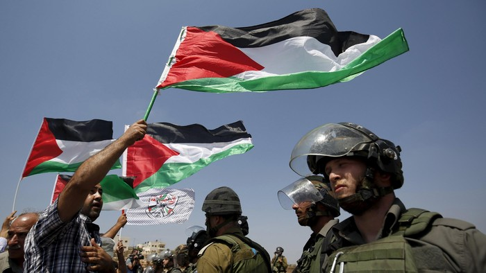 A Palestinian protester holds a Palestinian flag as he stands in front of Israeli border policemen during a protest against Jewish settlements in the West Bank village of Nabi Saleh, near Ramallah September 4, 2015. REUTERS/Mohamad Torokman