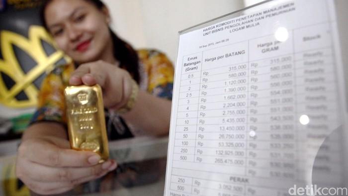 Seorang costumer service menunjukan emas batangan di butik emas, Gedung Antam, Jakarta, Jumat (18/9/2015). Harga emas antam hari ini kembali bergejolak menyusul pernyataan The Fed dalam rilisnya menyatakan mempertahankan suku buang acuannya, karena melihat kondisi perlambatan perekonomian dunia. Kebijakan itu dikeluarkan tak lama setelah perdagangan reguler untuk emas di Comex berakhir. (Foto: Rachman Haryanto/detikcom)