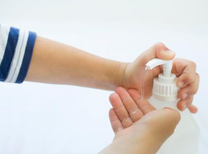 child disinfecting hands against the flu