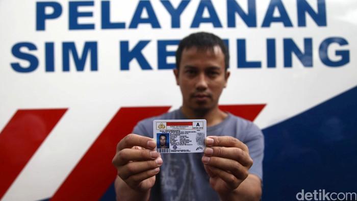 Petugas Polri membantu warga dalam pengurusan perpanjangan SIM di Hari Bebas Kendaraan Bermotor, Jakarta, Minggu (27/09/2015). Dalam HUT ke 60, Polantas meuncurkan  pembuatan maupun perpanjangan SIM dengan sistem online. Grandyos Zafna/detikcom.