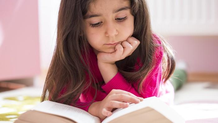 Anak membaca buku.