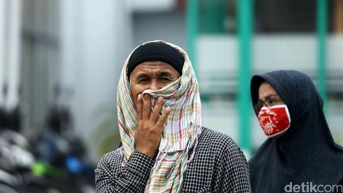 Warga Padang, Sumatera Barat, beraktifitas di  tengah kepulan kabut asap, Kamis (08/10/2015). Masih diselimutinya kawasan sekitaran padang membuat sejumlah warga harus mengenakan masker saat beraktivitas. Grandyos Zafna/detikcom.