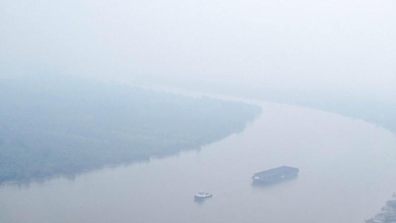 Kabut asap akibat kebakaran hutan dan lahan masih menyelimuti Kalimantan. Salah satunya adalah Sungai Barito dan kawasan kalimantan yang terlihat buram karena diselimuti asap pekat.