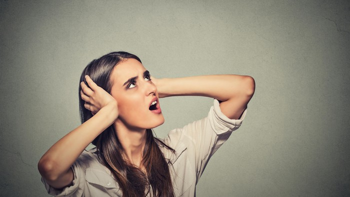 stressed woman covering ears looking up noise upstairs
