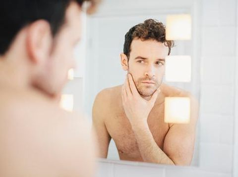 Young man checking his face in bathroom mirror