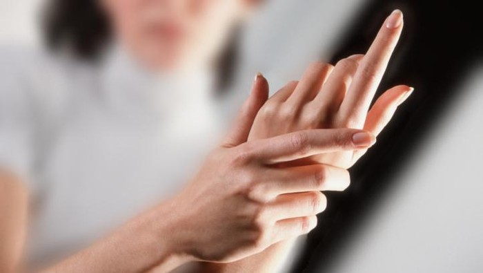 2000 --- Woman Rubbing Her Hands --- Image by  Royalty-Free/Corbis