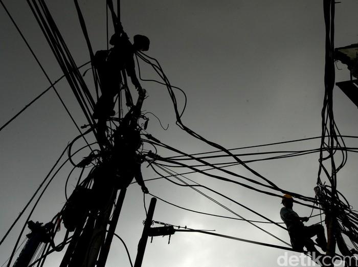 Perawatan kabel Telekomunikasi --- Pekerja melakukan perawatan kabel telekomunikasi di kawasan Pasar Blok A di Jalan Fatmawati, Jakarta, Senin (7/12/2015). (Ari Saputra/detikcom)