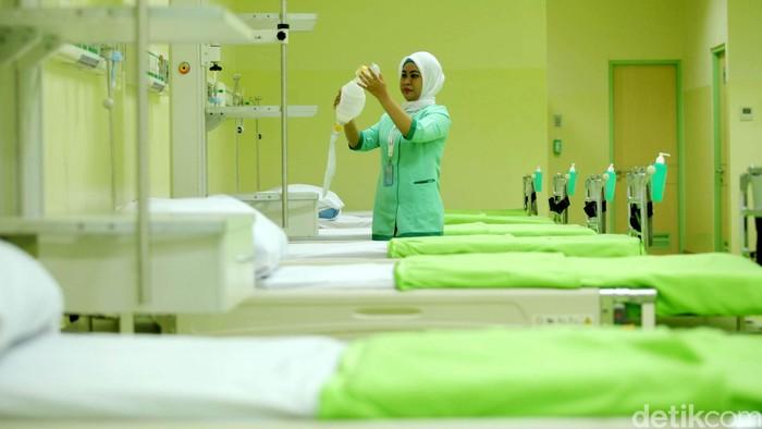 Seorang tenaga kesehatan merapikan tempat tidur pasien (Foto: Grandyos Zafna)