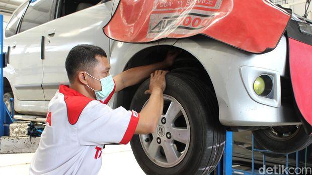 Mekanik mengecek kaki-kaki mobil