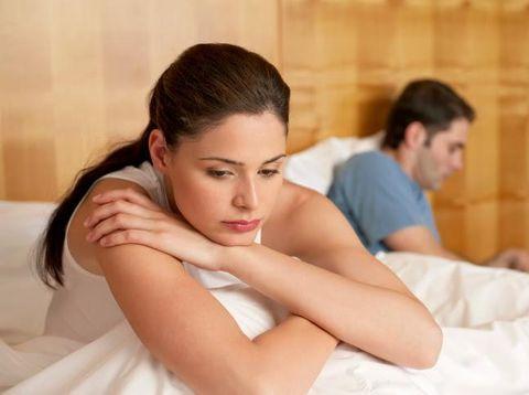 Sepasang suami istri yang terlihat bermasalah di atas ranjang.