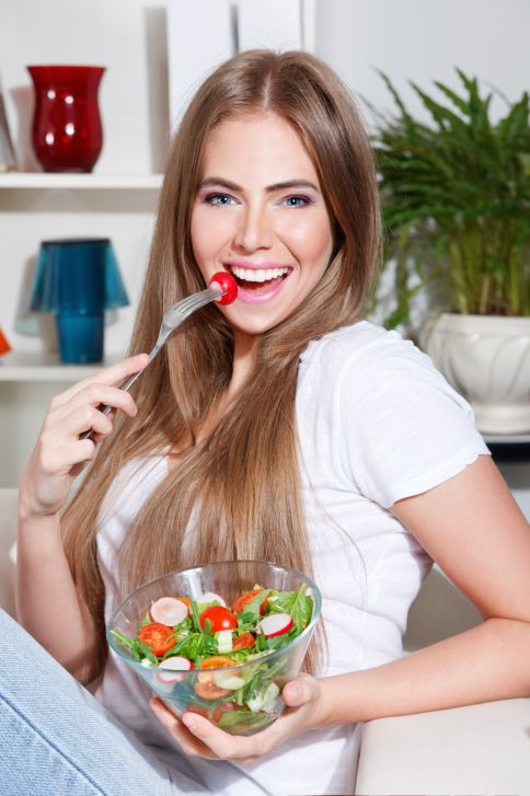 young woman eating fruit salad in bedroom