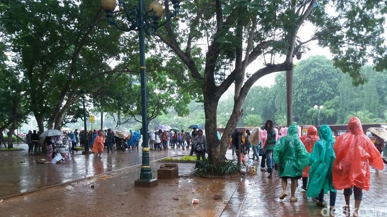 Wisatawan yang tetap semangat di Monas meski hujan turun. Foto: Kurnia Yustiana