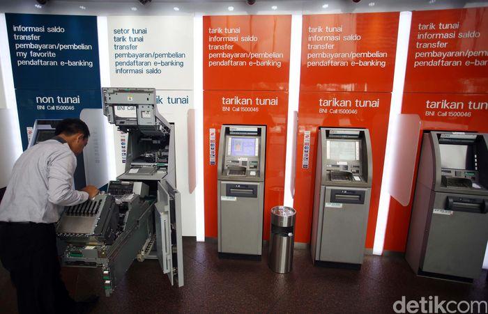 Seorang petugas mengecek mesin ATM.