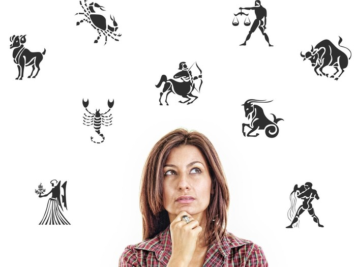 woman surrounded with zodiac signs thoughtfully looking up with