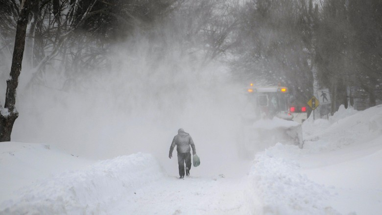 A man walks near a snow plow after a winter storm hit Charlottetown, Prince Edward Island February 16, 2015. Canadian media reported that 80 cm (2.6 feet) of snow hit the province, breaking a single storm record. REUTERS/Nathan Rochford (CANADA - Tags: ENVIRONMENT DISASTER SOCIETY)