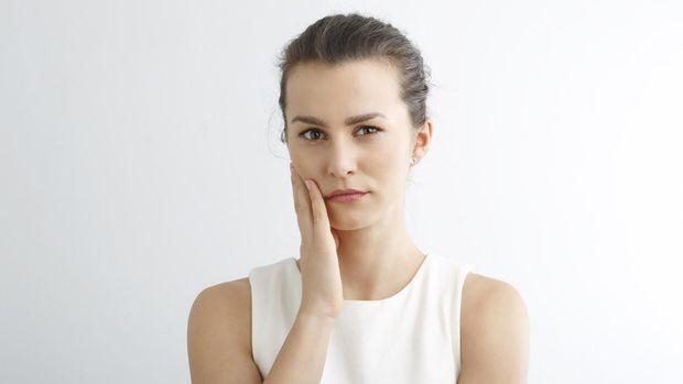 Ilustrasi seorang wanita yang sedang sakit gigi dan gusi