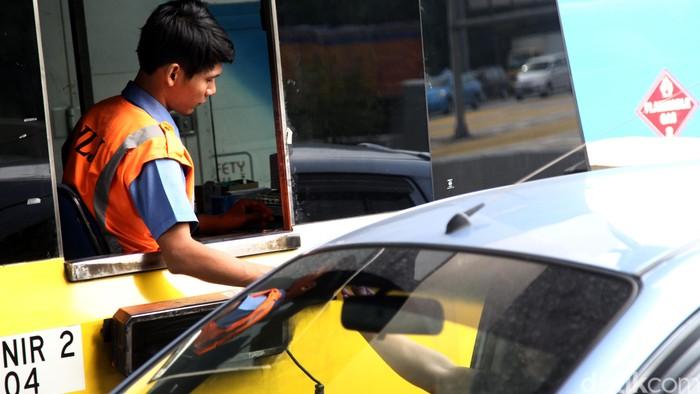 Petugas melalukan proses pengaturan pembayaran tol di Pintu Gerbang Tol Cikunir 2, Bekasi, Jawa Barat, Selasa (16/2/2016). Setelah terjadinya atap rubuh pada minggu kemarin tampak suasana gerbang tol berjalan normal meski atap rubuh masih terlihat. Dibagian atap yang rubuh disanggah dengan besi berukuran besar agar bisa dilewati kendaraan. Agung Pambudhy/Detikcom.